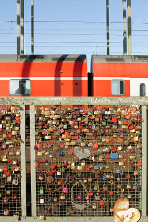 Cologne, Germany - February 2, 2014  Love locks, chains and hearts at the fence of the Hohenzollern bridge with a red train in the background on February 02, 2014 in Cologne