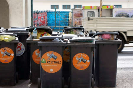 contiguous: The Photography of contiguous garbage cans on a street in Vienna