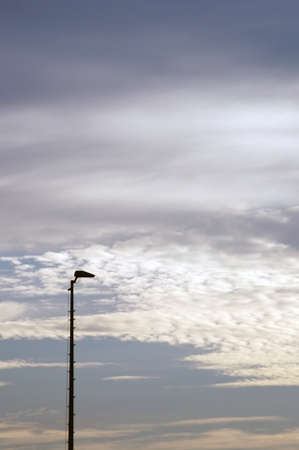 cloud formations: The photograph of a street lamp against a blue sky with cloud formations