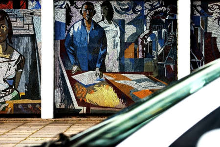 conquers: Potsdam, Germany - August 11, 2012   The mosaic painting  Man conquers the cosmos   FRITZ EISEL on the side of a house in Potsdam with a passing car on August 11, 2012 in Potsdam