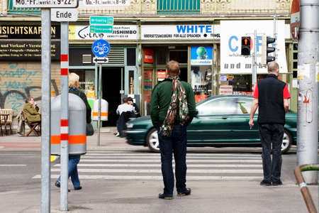 Vienna, Austria - March 30, 2014  People sitting at a shop across the street from pedestrians who are standing at a traffic light on March 30, 2014 in Vienna