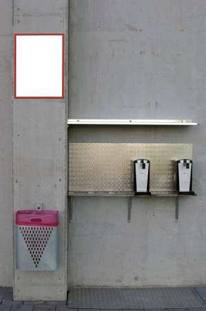 The photograph of a beer dispenser and a trash can on a concrete wall                   photo