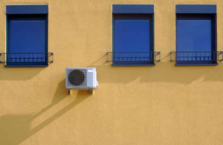 The Photography of windows and air conditioning on a colorful plaster facade in sunlight                Stock fotó