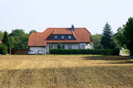 well maintained: The photograph of a family home behind a plowed field                      Stock Photo