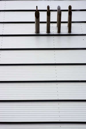 The photograph of a modern house facade made of corrugated sheet metal lined up with smoldering pipes. photo
