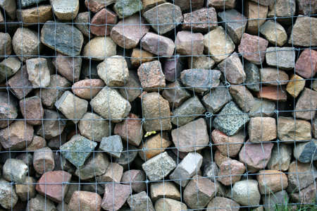 demarcation: The photograph of a fence made of fieldstone and wire mesh.