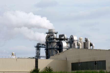 De foto van een rokerige schoorsteen, buizen en ketels van een industriële installatie.