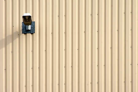 The photograph of a street lantern on a corrugated metal facade.