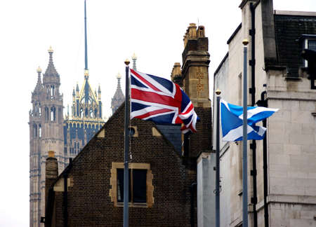 scottish flag: London, UK - November 27, 2014: The British and Scottish flag waving in front of building parts of the Westminster palace with the Victoria Tower in the background on November 27, 2014 in London.