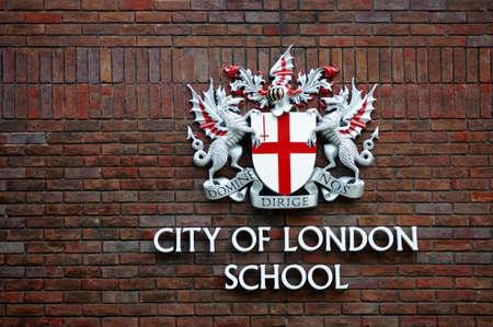 city coat of arms: London, UK - November 28, 2014: The coat of arms of the City of London School on a brick facade on November 28, 2014 in London.