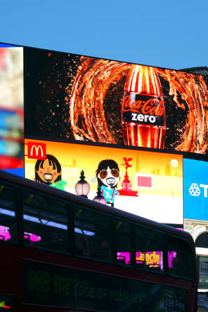 London, UK - November 28, 2014: A red double-decker crosses a large advertising space on the Piccadilly Circus on November 28, 2014 in London.