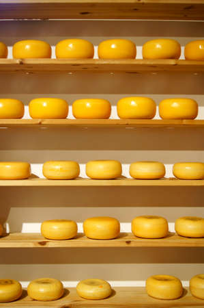 Stacked cheeses on wooden shelves,