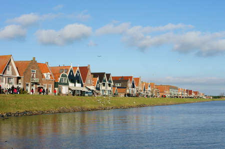 volendam: Volendam, Netherland - December 31, 2014: Visitors and Tourists walk in good weather along the promenade of the city Volendam on December 31, 2014 in Volendam.