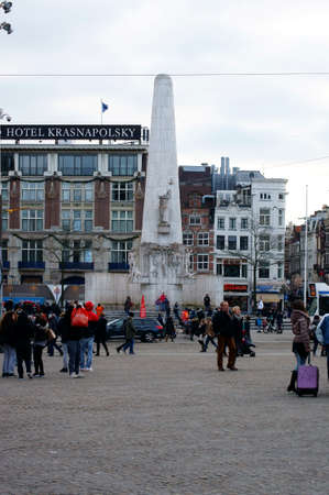 dam square: Amsterdam, Netherlands - December 29, 2014: Groups of people standing and going along the Dam square at the National Monument on December 29, 2014 in Amsterdam.
