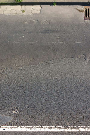 gully: The top view of the crumbling asphalt of a highway with a gully.
