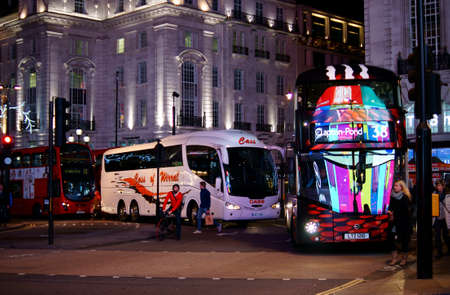 London, UK - November 29, 2014: Tourist buses and a red double-decker stand at a crossroad at the Piccadilly Circus and reflect the advertising space on November 29, 2014 in London.
