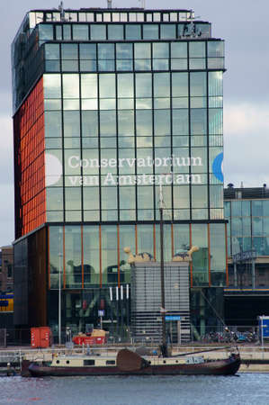 old ship: Amsterdam, The Netherlands - December 31, 2014: The modern building of the Conservatory of Amsterdam where a old ship anchored on December 31, 2014 in Amsterdam. Editorial