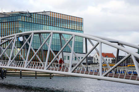 anorak: Amsterdam, The Netherlands - December 31, 2014: A little boy in a red anorak drives in Amsterdam on 31 December 2014 over the Mr. JJ van de Velde bridge. Editorial