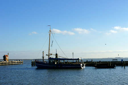 volendam: A fishing boat moored in the harbor of Volendam in fine weather. Stock Photo