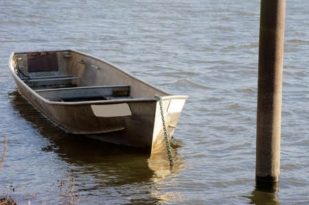 chaining: An old rowing boat made of sheet metal floats on the water and is chained on the banks of a river. Stock Photo