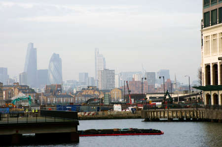 southwark: London, UK - November 28, 2014: A road construction site in the financial hub of Canary Wharf overlooking the skyline and skyscrapers of Southwark on November 28, 2014 in London.