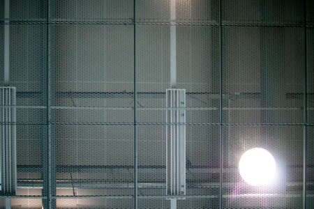 halogen lighting: The bottom of a round, luminous ceiling lamp behind a metal grid.