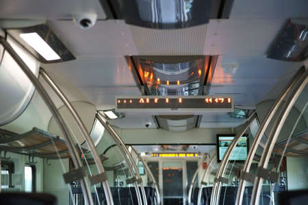 compartment: A train compartment with grab bars and luggage racks.