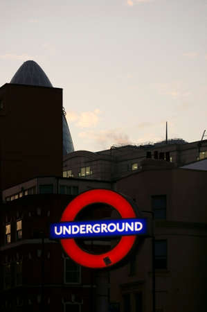 30 st mary axe: London, UK - November 29, 2014: The illuminated sign of the London Underground during a sunset with the top of the 30 St. Mary Axe tower in the background on November 29, 2014 in London. Editorial