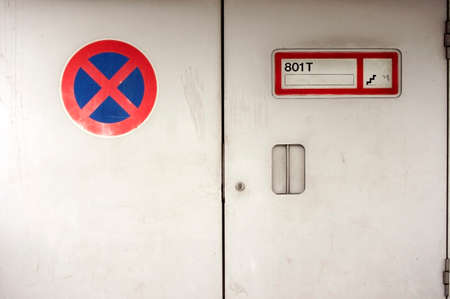 stopping: Two signs on the steel door of a loading ramp: Stopping restriction and lift plate.