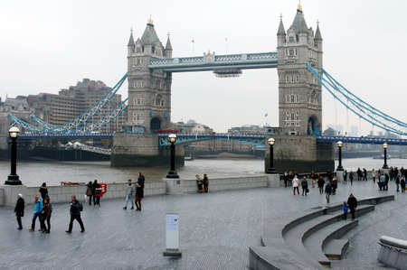 southwark: London, UK - November 28, 2014: The side view of the Tower Bridge with a promenade of the district of Southwark where people walk along on November 28, 2014 in London.