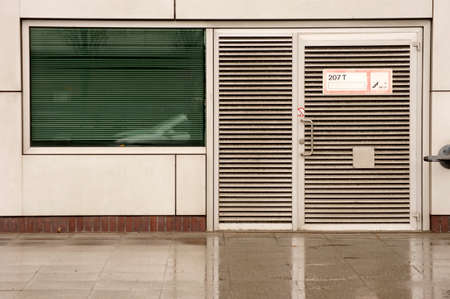 louvered: A striking louvered door with signs in the rain.
