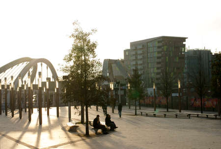 wembley: London, UK - November 28, 2014: Visitors to Wembley Park sit on park benches and enjoy the sun in backlight on November 28, 2014 in London.