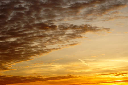 cloud formations: The bright and yellow sunset on a sky with various abstract and cloud formations.