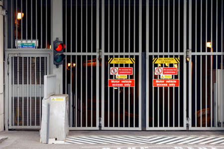 driveway: A car park entrance or driveway with a traffic light and a grid. Editorial