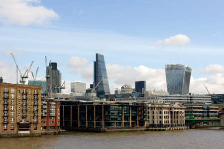 London, UK - March 31, 2015: The skyline of the office complex of the City of London behind homes and historic buildings on the banks of the River Thames on March 31, 2015 in London.