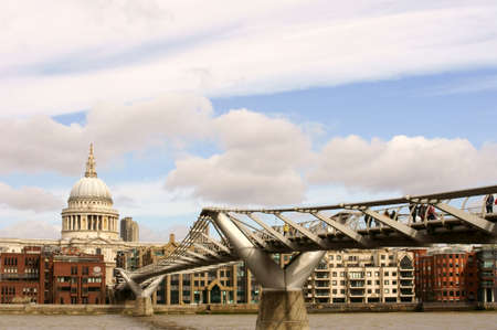 st  paul   s cathedral: London, UK - March 31, 2015: Visitors and passers going over the modern steel construct of the Millennium Bridge with the St Paul \\ \ s Cathedral at his end on March 31, 2015 in London.