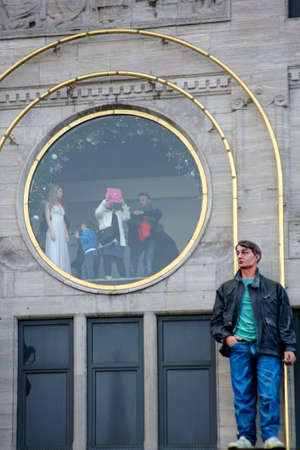 picture window: Amsterdam, The Netherlands - December 29, 2014: Tourists photographing with a Tablet PC from a round picture window of the wax museum Madame Tussaud on December 29, 2014 in Amsterdam. Editorial