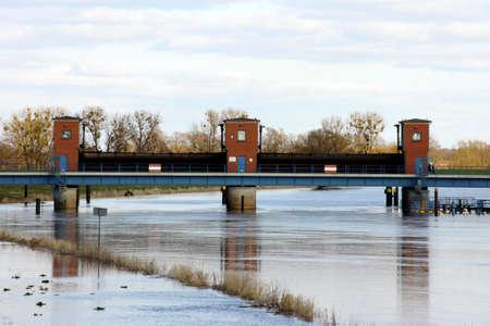 floodgates: A sluice with open floodgates on a river.