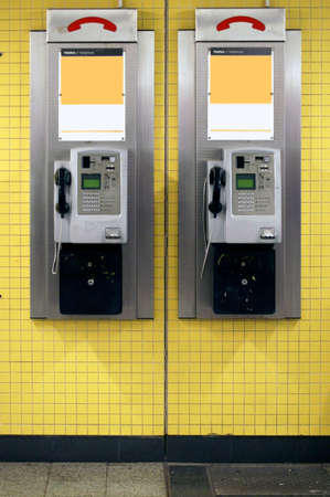 pay wall: Two old nostalgic payphones hanging on the tiled wall of a subway tunnel.