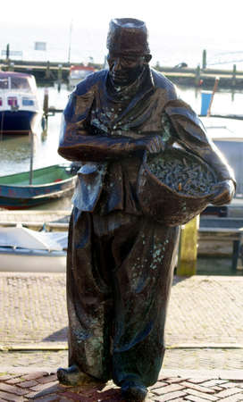 verdigris: Volendam, The Netherlands - December 31, 2014: The sculpture The Fisherman of the artist Jan van Baarsen on the promenade of the town of Volendam on December 31, 2014 in Volendam.