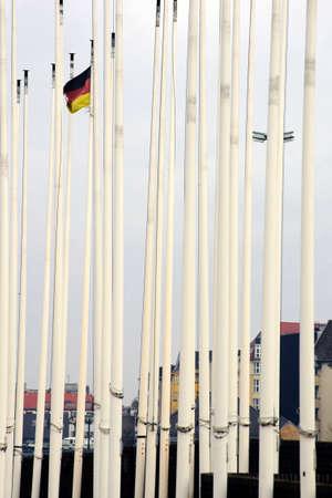 flagpoles: A German flag waving between closely juxtaposed flagpoles.
