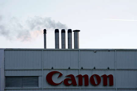 checkerplate: Amsterdam, Netherlands - December 30, 2014: The logo of the company Canon on a facade cladding with chimneys during a sunset on December 30, 2014 in Amsterdam.