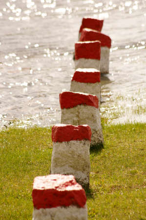 boundary: A series of red boundary stones in a river. Stock Photo