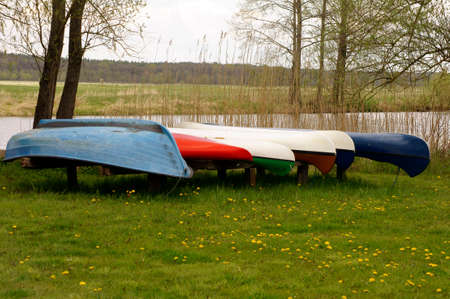 jacked: A number of canoes and rowboats standing in a row on a meadow and jacked by the river. Archivio Fotografico