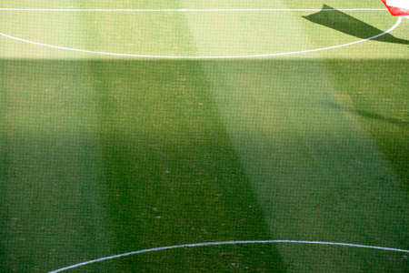 kickoff: The green lawn of a soccer field with the kick.off circle markings and a shadow of a waving flag behind a safety net. Stock Photo