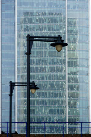 irregular shapes: Streetlights in front of a bridge and a glass facade of a modern building.