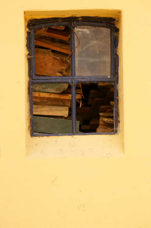 nostalgic: The nostalgic window of a barn with fire logs behind the window. Stock Photo