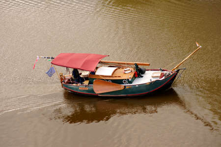 replica: The replica of an ancient Chinese boat, a junk in the waters of a port.