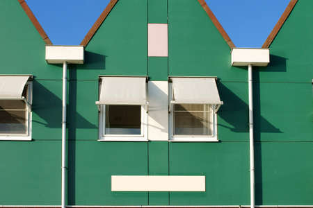 house gable: A Dutch house with a triangular gable and and sunscreen on the windows.