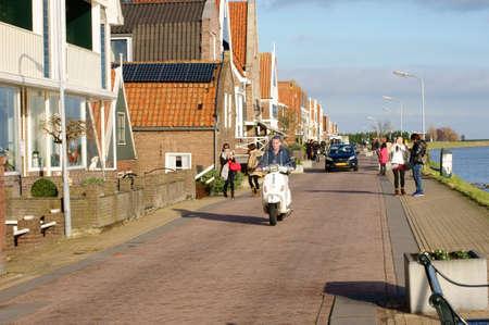volendam: Volendam Netherlands December 31 2014: Vehicles and pedestrians walk the drive along the promenade of the city Volendam on December 31 2014 in Volendam.